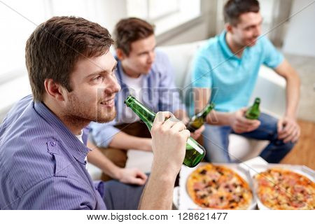 friendship, alcohol, people, celebration and holidays concept - close up of happy male friends clinking beer bottles and eating pizza at home