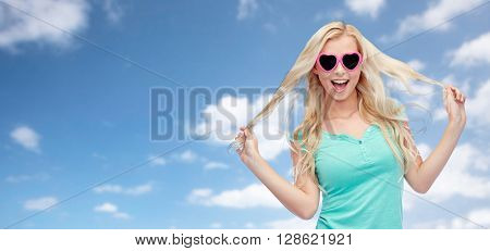 emotions, expressions, summer and people concept - smiling young woman or teenage girl in sunglasses holding her strand of hair over blue sky and clouds background