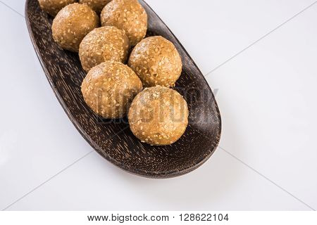 tilgul or til gul laddu, isolated on white background, showing wooden plate full of laddu in background, selective focus