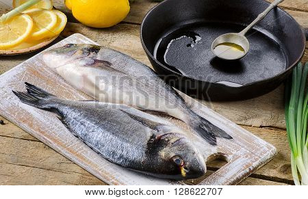 Fresh Uncooked Dorado Or Sea Bream On Rustic Wooden Board.