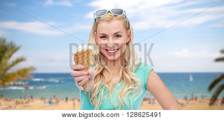 summer holidays, travel junk food and people concept - young woman or teenage girl in sunglasses eating ice cream over exotic tropical beach with palm trees and sea background