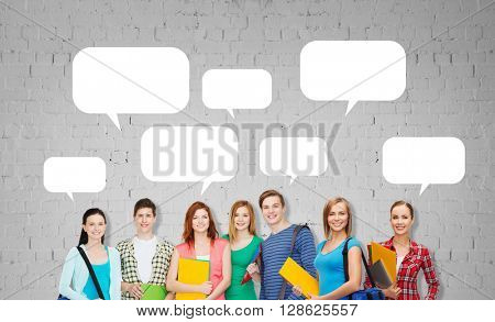 education, school and people concept - group of smiling teenage students with folders and school bags over gray brick wall background with empty text bubbles
