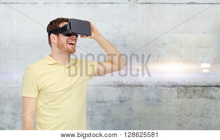 3d technology, virtual reality, entertainment and people concept - happy young man with virtual reality headset or 3d glasses over gray concrete wall background