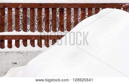 Winter landscape backyard private farmhouse with a red fence and snowbank in foreground