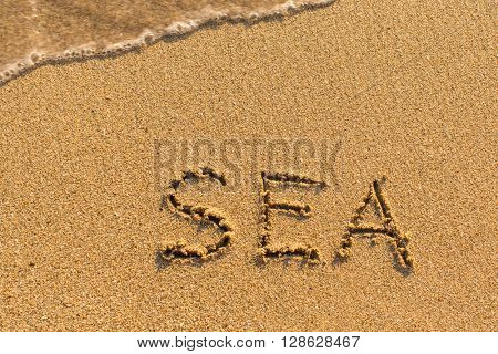 Sea - inscription by hand on the beach.