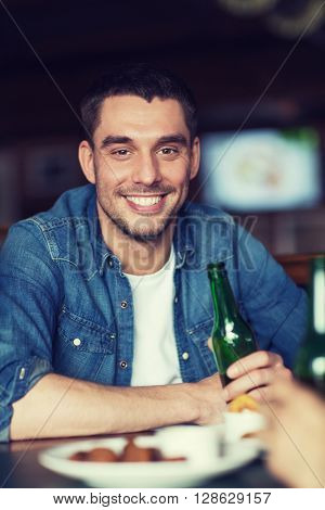 people, leisure and bachelor party concept - happy young man drinking beer at bar or pub
