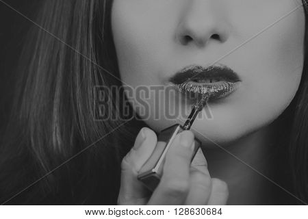 Beautiful girl on a dark background with exquisite lipstick. A beautiful red shade of lipstick is not seductive lips.