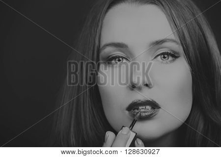 Beautiful girl on a dark background with exquisite lipstick. A beautiful red shade of lipstick is not seductive lips. Photo for fashion magazines and websites.