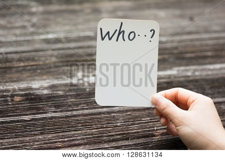 holds card with text who on old wood plate