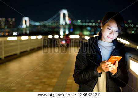Young woman using her mobile phone at night