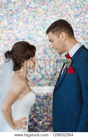 Wedding couple in rage. Beautiful bride in white dress and veil with handsome groom in blue suite standing and angry in each other indoors against beautiful colored background bokeh. Close-up portrait of man and girl looking on each other in angry poses.