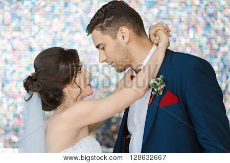 Wedding couple in love. Beautiful bride in white dress and veil with handsome groom in blue suite standing and embracing each other indoors against beautiful colored background bokeh like their dreams.