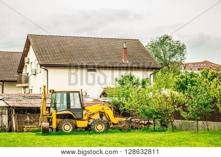 Shot made to an excavator in a yard prepairing to work in a cloudy day