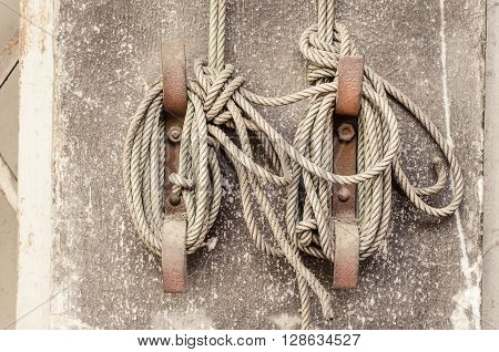 Knot rope tied around stake on cement wall