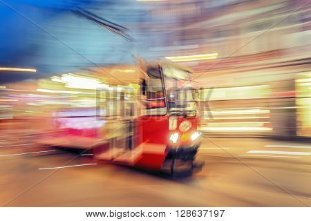 Creative abstract city transportation and business travel technology industrial concept: red tram on urban city street with motion blur effect. Katowice.