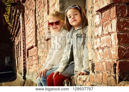 Modern children wearing casual jeans clothes posing on the city street by a brick wall. Kid's fashion.