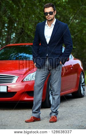 Handsome young man in his new sports car.