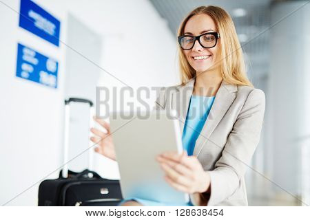 Young businesswoman sitting with touchpad in the airport