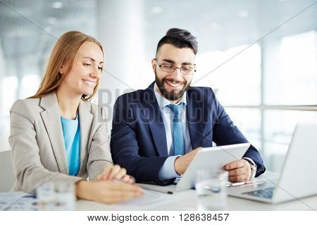 Man and woman discussing business on touchpad