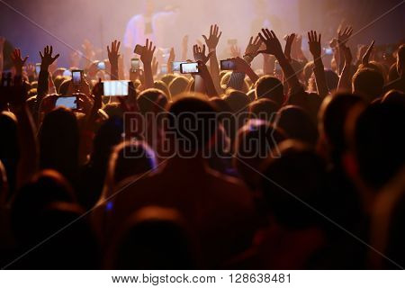 Fans listening to their performer with hands raised