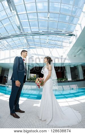 Wedding couple in love. Beautiful bride in white dress and veil and brides bouquet with handsome groom in blue suite standing and looking each other indoors at pool. Full lenght portrait of man and girl. Concept of wedding celebration in vacation. Fisheye