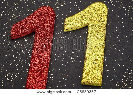 Number eleven red yellow color over a black background. Anniversary. Horizontal