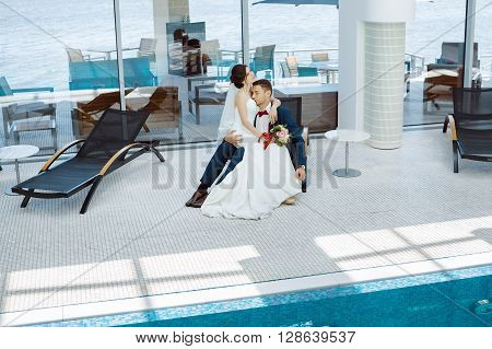 Wedding couple in love. Beautiful bride in white dress and veil and brides bouquet with handsome groom in blue suite sitting on plank bed and embracing each other indoors at pool. Full lenght portrait of man and girl. Concept of wedding celebration