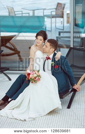 Wedding couple in love. Beautiful bride in white dress and veil and brides bouquet with handsome groom in blue suit sitting on plank bed and embracing each other indoors at pool. Full lenght portrait of man and girl. Concept of wedding celebration