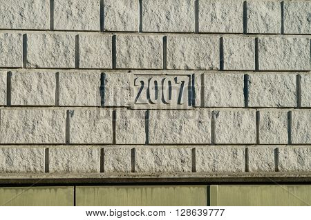 Grey quarry stone wall with inscription 2007 in the middle.