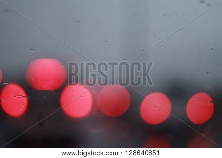 Waterdrops or raindrops and lights bokehon a glass surface (Selective focus)