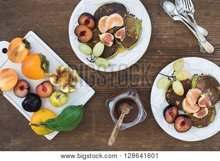 Breakfast set. Homemade zucchini pancakes with fresh plum, tangerine, grapes, figs and honey in white ceramic plates over rustic wooden background, top view