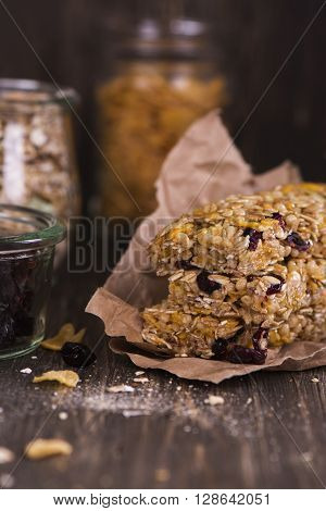 Stack of cereal bars with oat, cranberry, nuts and corn flakes over wooden table