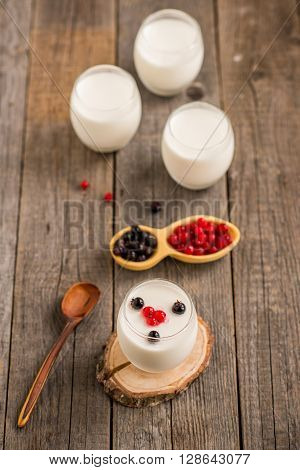fresh homemade yoghurt with berries on rustic wooden background