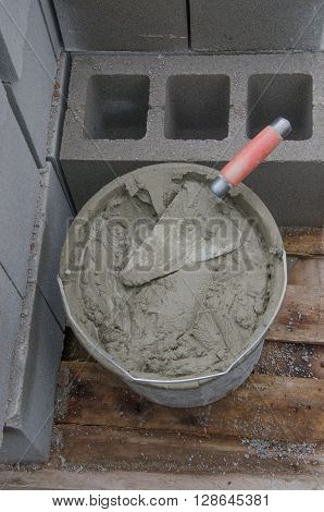 bucket with cement and trowel on tiles.