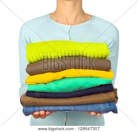 Woman hold clothes pile against white background close up