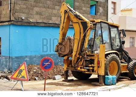 Backhoe on a construction site with caution signs