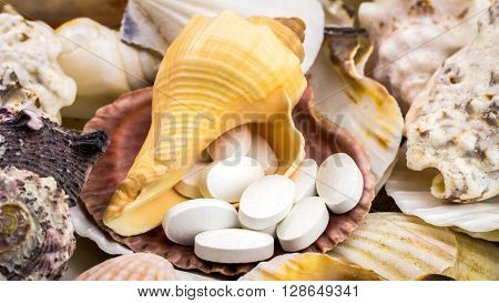 Calcium natural food supplement pills on the beautiful mixed seashells background