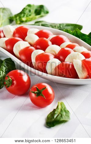 dish with sliced mozzarella cheese balls and ripe cherry tomatoes in caprese salad on the white table. vertical format