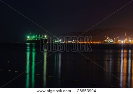 Port of Eilat at night.  Large cargo ship anchored in front of the port.
