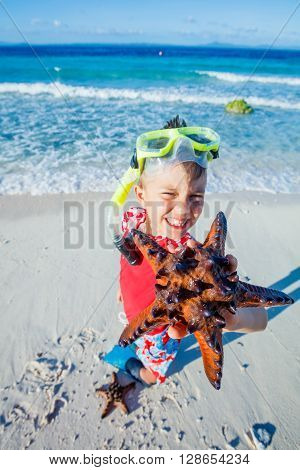 Joyful boy on the tropical beach with equipment to scuba diving and starfish. Focus on the starfish.