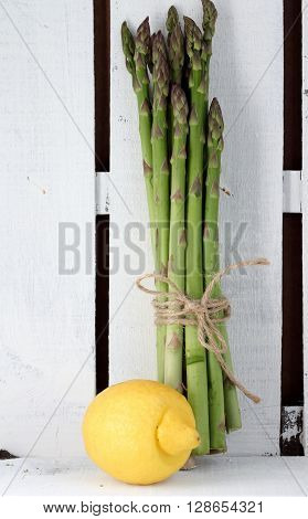 Simple composition . Organic asparagus tied with brown string and a lemon in a rustic white painted wooden crate