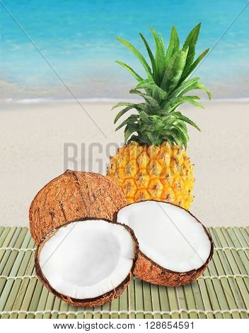 Fresh pineapple with green leaves and two halves of brown coconut. Beach sand and blue ocean on background.