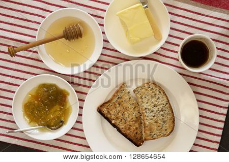 Buttered toast, honey, marmalade and coffee for breakfast.