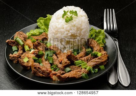 Stewed beef with boiled white rice on black plate.