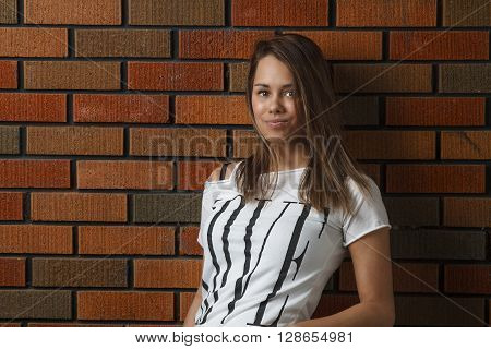 twenty something girl leaning against a brick wall