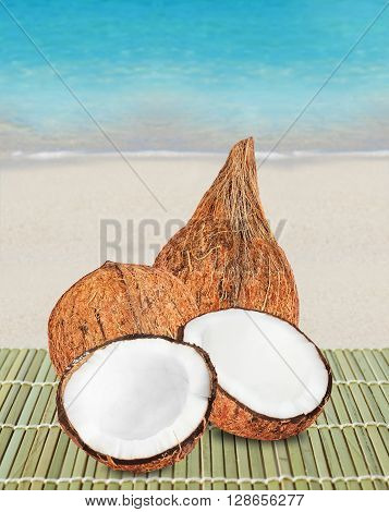 Fresh closed coconuts and two halves of open coconut on beach. white sand and blue ocean waves on background.