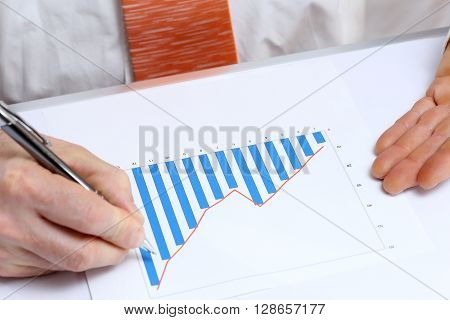 business man is drawing a diagram on desk
