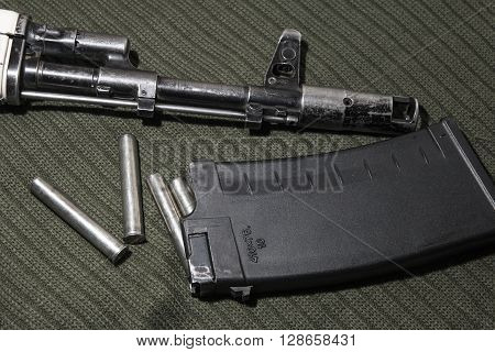 automatic rifle with cartridges on a green background