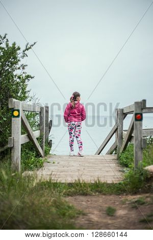 Young school girl resting on dock and enjoying look at ocean