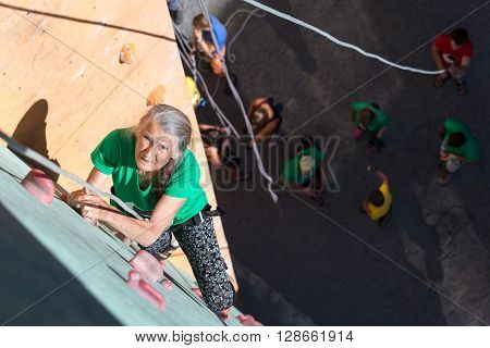 Elderly Female Moving Up on Outdoor Climbing Wall Sporty Clothing on Fitness Training Intense but Positive Face Using Rope and Belaying Gear